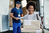 Portrait of satisfied African American woman holding her delivered packages.
