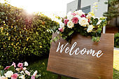 Welcome board with rose bouquet at outdoor wedding venue.