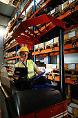 Forklift driver checking his daily schedule in a distribution warehouse.