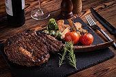 grilled tomahawk ribeye steak on black stone plate