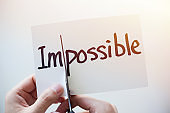 Cutting Out the Word Impossible and Possible on Paper with Scissors