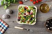 Italian salad with fresh vegetables with black olives and Parmesan cheese.