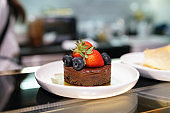 Homemade dark chocolate cake with cookies crust pie, topped with fresh strawberry, blueberry on marble table and blurred background.