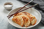 Fried dumplings with meat (beef, pork) or seafood, cabbage and spices in a white plate with soy sauce and sesame seeds.  Traditional Asian food. The Japanese have gyoza, Chinese dim sums. Selective focus