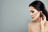 Glamorous woman fashion model with makeup and jewelry earrings with black gem portrait