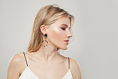 Portrait of fashion pretty woman with blonde hair, makeup and golden earrings on white background. Perfect female profile
