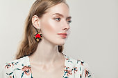 Perfect beautiful woman wearing fashion golden earrings with red heart on white background, profile