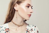 Elegant woman with fashion golden chain earrings and pearls necklace on white background