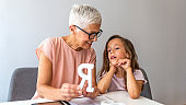 Mature female therapist helping girl in speech therapy exercise