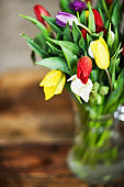 Flower background: bouquet of colorful tulips in a glass vase on a natural wooden background, postcard, mocap for mother's day greetings, international women's day
