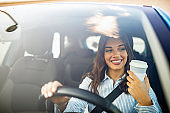 Woman sipping a coffee while driving a car