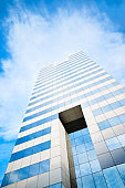 The top of a modern skyscraper or commercial building with glass windows and blue sky with clouds in the background