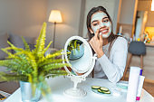 Young beautiful woman applying homemade facial mask at home