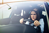 Stressed woman driver sitting inside her car.