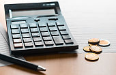 A calculator, coins and tax forms on the table to reckon