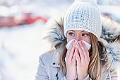 Girl with allergy symptom blowing nose