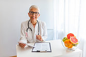 Confident nutritionist working at desk with fresh fruit.