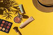 Eyeshadows, powder blush, make up brush on bright yellow background