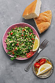 Middle Eastern or Arabic dish tabbouleh salad with pita bread on a gray background. .Top view