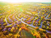 Sun burst of Fall autumn colors suburb neighborhood above Central Texas