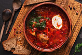 Traditional Russian Ukrainian borscht red soup with rye bread on a dark background. Borsch with meat, sour cream and dill. Overhead, copy space.
