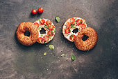 Homemade bagel sandwich with soft cheese, cherry tomatoes and basil sprinkled with sesame and flax seeds, dark rustic background. Top view, flat lay, place for text.