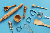 Flat lay variety of kitchen utensils for cooking on a blue background. View from above
