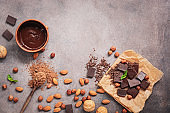 Melted chocolate, cocoa powder, chocolate slices, nuts and mint on a dark rustic background. Top view, flat lay,copy space