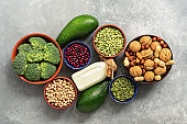Vegan protein source. Healthy diet concept for vegans and vegetarians. Vegetables, milk, legumes, seeds, nuts on a gray concrete background. Overhead.