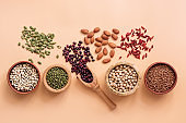 Healthy vegan and vegetarian super foods, beans, pumpkin seeds, chickpeas, buckwheat, mung beans, almonds and goji berries on a pastel pink background. Top view, flat lay, copy space.