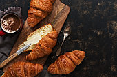 Fresh croissants with butter and hot coffee on a cutting wooden board, dark rustic background. Top view, flat lay,copy space.