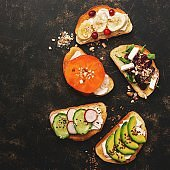 A variety of vegan sandwiches with vegetables and fruits on a dark rustic background. Top view, flat lay. The concept of healthy eating.