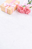 May mothers day handmade giftbox idea concept, beautiful blooming carnations with baby pink ribbon bow gift isolated on modern marble desk, close up, copy space, mock up