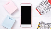 Abstract online shopping, mobile payment concept design element, colorful cart and paper bags on white wooden table background.
