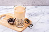 Popular Taiwan drink - Bubble milk tea with tapioca pearl ball in drinking glass on marble white table wooden tray background, close up, copy space