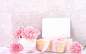 May mothers day handmade giftbox wishes photography - Beautiful blooming carnations with pink ribbon box isolated on fair-faced gray background desk, close up, copy space, mock up