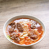 Beef noodle ramen meal with tomato sauce broth in bowl on bright wooden table, famous chinese style food in Taiwan, close up, top view, copy space