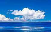 The tropical sea under the blue sky and clouds