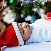 Beautiful one week old newborn baby wrapped in blanket near Christmas tree with colorful garland lights on background. Closeup of cute little child sleeping peaceful. Family, Xmas, birth, new life.