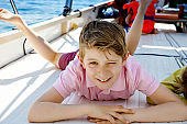Happy blonde kid boy enjoying sailing boat trip. Family vacations on ocean or sea on sunny day. Healthy beautiful school child smiling and having fun on yacht. Coastline with villages and nature