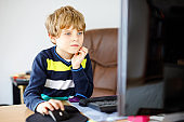 Little kid boy making school homework on computer notebook. Happy healthy child searching information on internet. New media education, kid watching learning lessons on pc. Virtual classroom.