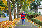Happy little boy running on autumnal street after school. Kid happy about school vacations. Child with autumn fashion clothes walking in the city.