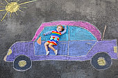 Adorable little toddler girl playing with colorful chalks and painting big car picture on asphalt. Happy baby child playing outside. Creative leisure for children outdoors in summer