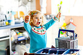 Cute little toddler girl helping in the kitchen with dish washing machine. Happy healthy blonde child sorting knives, forks, spoons, cutlery. Baby having fun with helping housework mother and father.