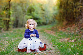 Cute little toddler girl sitting on suitcase in autumn park. Happy healthy baby enjoying walking with parents. Sunny warm fall day with child. Active leisure and activity with kids in nature.