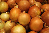 Pile of orange gold color raw onions in the market for background