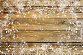 Beautiful white snowflakes on a wooden background. Beautiful backdrop for design.