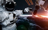 Astronaut at spacewalk against international space station. Science fiction art. Elements of this image furnished by NASA