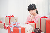 Portrait of little cute asian girl praying by pie of gift box, Asian teenage girl making a wish for christmas concept