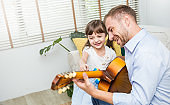 Portrait of family caucasian man little girl play guitar and maracas in living room. Daddy girl singing smiling. Happiness harmony father'™s day concept